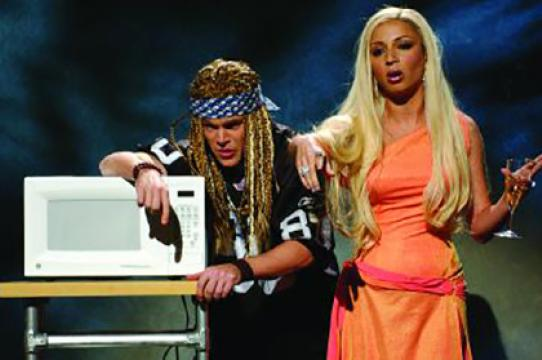 "In a Saturday Night Live skit, rocker Axl Rose (Matt Damon) prepares to indulge in the latest creation by fashion designer Donatella Versace (Maya Rudolph)--her microwavable ""Versace Pockets."" (Photo: NBC/Norman Ng)"
